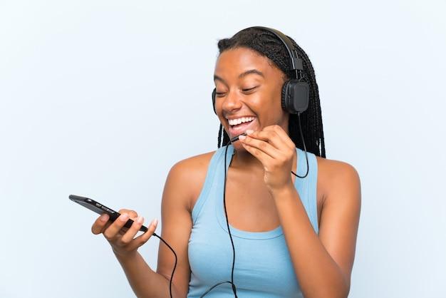 Afroamerikanerjugendlichmädchen mit hörender musik des langen umsponnenen haares mit einem mobile