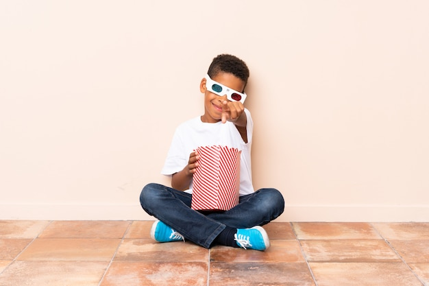 Afroamerikanerjunge, der popcorn hält und auf die front zeigt