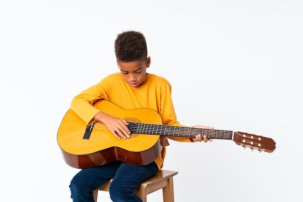 Afroamerikanerjunge mit gitarre über getrenntem weiß