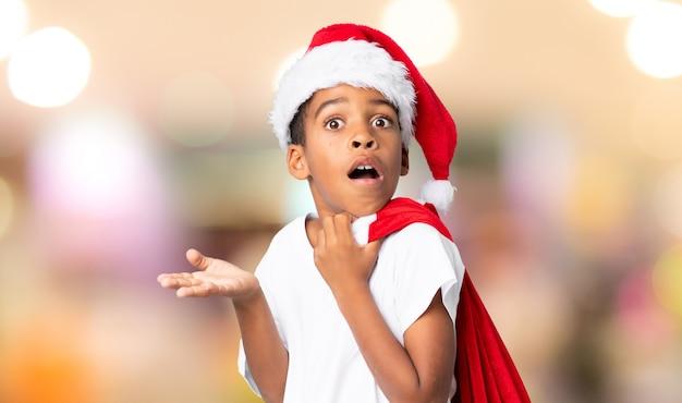 Afroamerikanerjunge mit weihnachtshut und nehmen einer tasche mit den geschenken, die überraschungsgeste über unscharfer wand tun