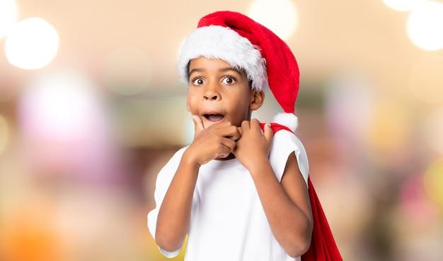 Afroamerikanerjunge mit weihnachtshut und nehmen einer tasche mit geschenken über unscharfem hintergrund