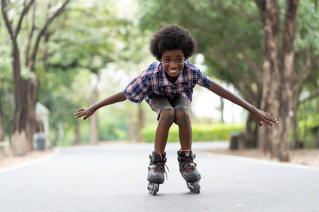 Afroamerikanerjunge reitet auf rollschuhen oder rollerblades im freien.