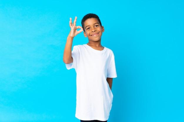 Afroamerikanerjunge über dem blau, das okayzeichen mit den fingern zeigt