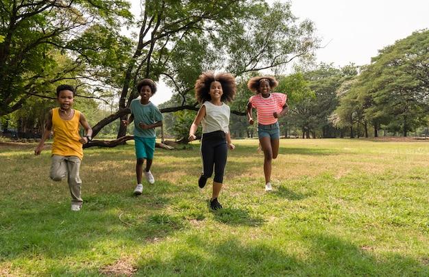 Afroamerikanerkinder, die im sommer im park genießen und laufen