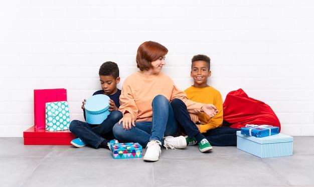 Afroamerikanerkinder mit ihrer mutter unter vielen geschenken für weihnachtsfeiertage