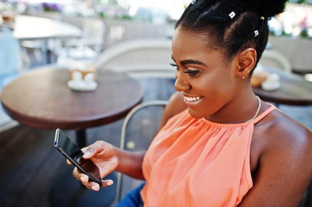 Afroamerikanermädchen, das auf tabelle von caffe mit handy sitzt.