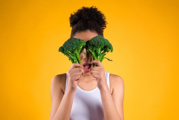 Afroamerikanermädchen, das brokkoli lokalisiert hält.