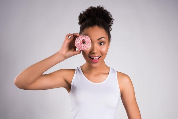 Afroamerikanermädchen, das donut lokalisiert hält.