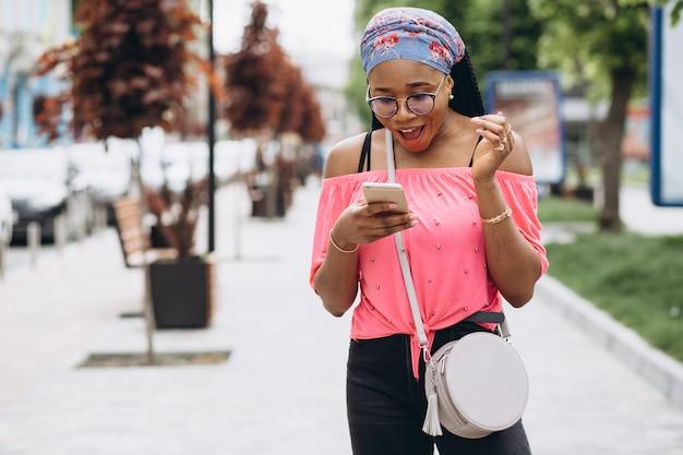 Afroamerikanermädchen, das ihr handy auf der straße benutzt