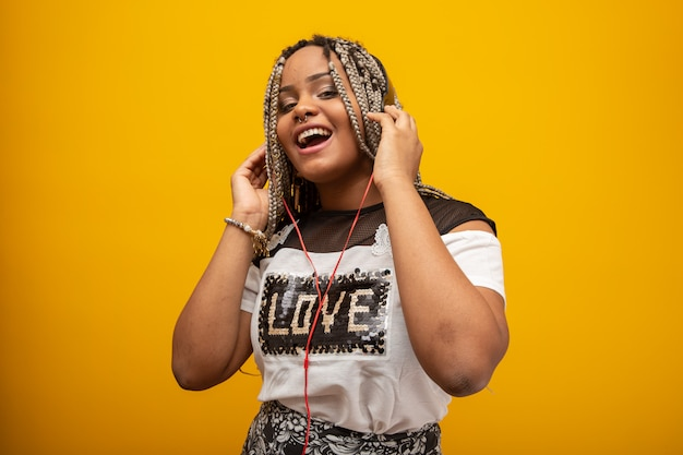 Afroamerikanermädchen, das musik auf kopfhörer auf gelb hört