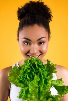 Afroamerikanermädchen, das salat lokalisiert hält.