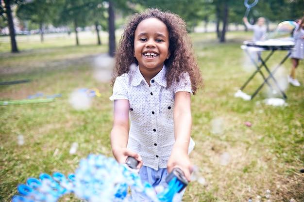 Afroamerikanermädchen, das seifenblasen macht