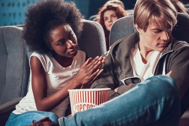 Afroamerikanermädchen entschuldigt sich bei frustriertem kerl im kino