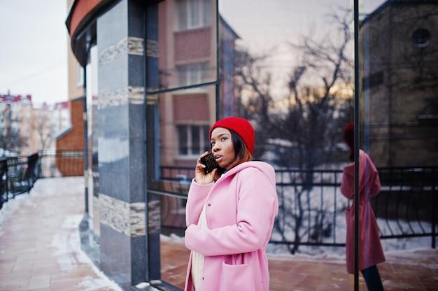 Afroamerikanermädchen im roten hut und im rosa mantel an der straße der stadt gegen das errichten am wintertag mit handy.