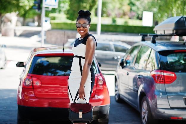 Afroamerikanermädchen in der sonnenbrille, im schwarzweiss-kleid und in der handtasche warf gegen autoparken auf.
