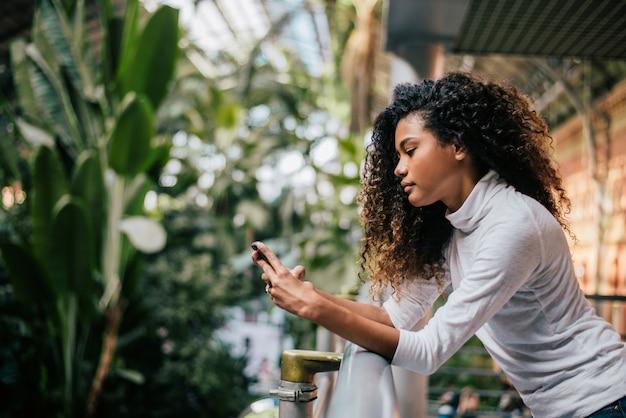 Afroamerikanermädchen mit einem schönen gelockten haar, das ihr telefon betrachtet.