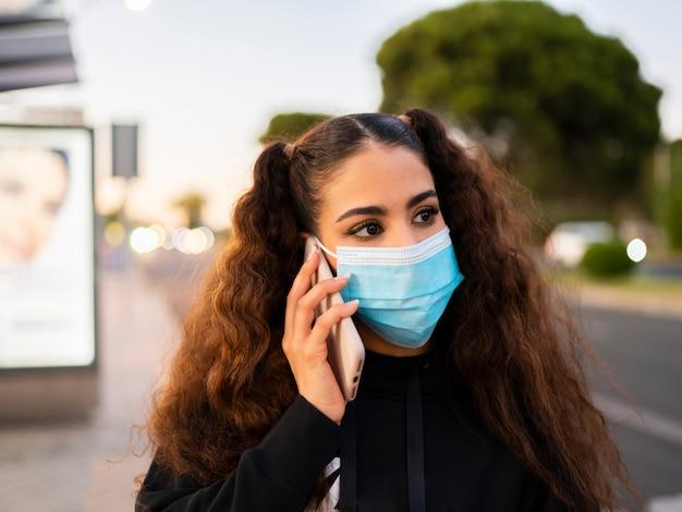 Afroamerikanermädchen mit einer maske, die ihr telefon benutzt