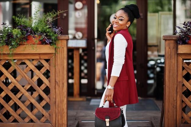 Afroamerikanermädchen mit handtasche stellte im freien von steets stadt auf und sprach am telefon.