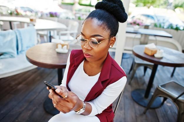 Afroamerikanermädchen tragen in den gläsern mit dem handy, das am außenkaffee sitzt.
