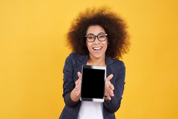 Afroamerikanermädchen wirft mit der schwarzen lokalisierten tablette auf.