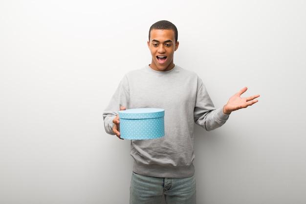 Afroamerikanermann auf dem weißen wandhintergrund überrascht, weil ein geschenk gegeben worden ist