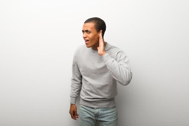 Afroamerikanermann auf weißem wandhintergrund hörend auf etwas, indem er hand auf das ohr setzt