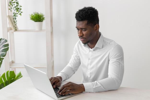 Afroamerikanermann, der am laptop arbeitet