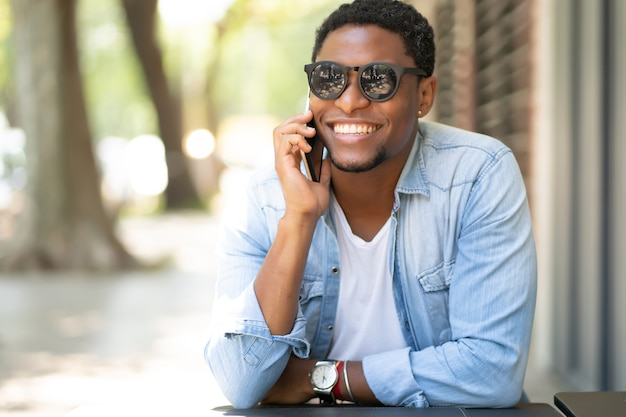Afroamerikanermann, der am telefon spricht, während er am kaffeehaus sitzt