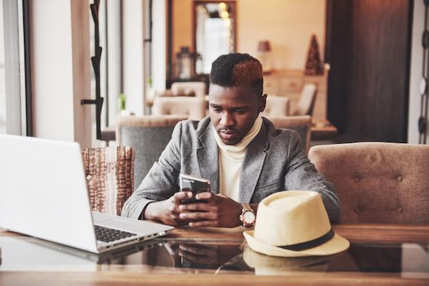 Afroamerikanermann, der an einem kaffee sitzt und an einem laptop arbeitet