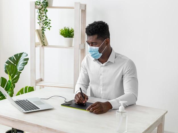 Afroamerikanermann, der an einer tablette arbeitet