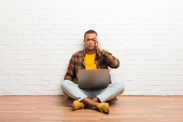 Afroamerikanermann, der auf dem boden mit seinem laptop unglücklich und mit etwas frustriert sitzt