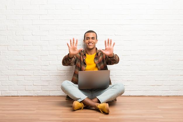 Afroamerikanermann, der auf dem boden mit seinem laptop zählt zehn mit den fingern sitzt
