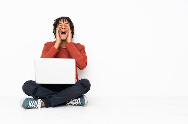 Afroamerikanermann, der auf dem boden sitzt und einen computer hält