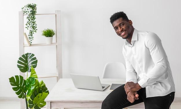 Afroamerikanermann, der auf dem schreibtisch sitzt