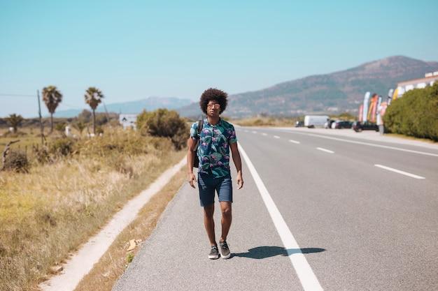 Afroamerikanermann, der auf straßenrand geht