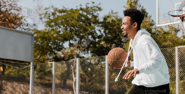 Afroamerikanermann, der basketball spielt