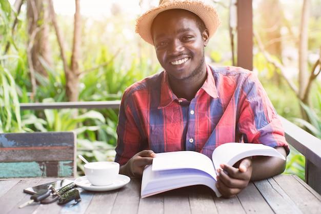 Afroamerikanermann, der ein buch mit kaffee, schlüssel und smartphone liest.