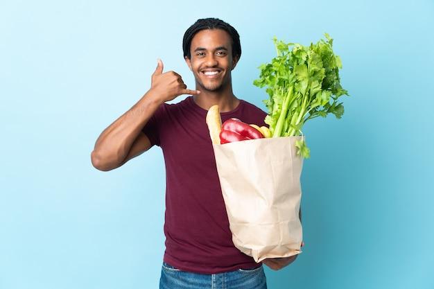 Afroamerikanermann, der eine einkaufstasche des lebensmittels auf blau hält, das telefongeste macht