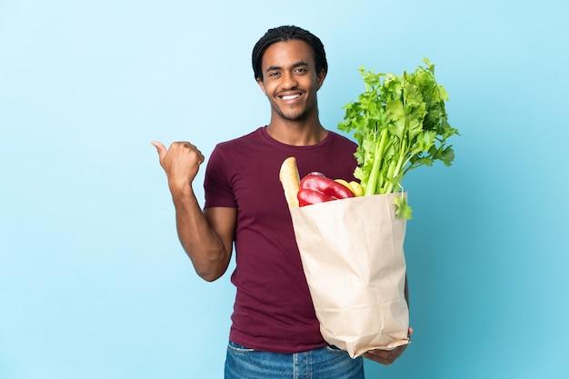Afroamerikanermann, der eine einkaufstüte des lebensmittels auf blau hält, das zur seite zeigt, um ein produkt zu präsentieren