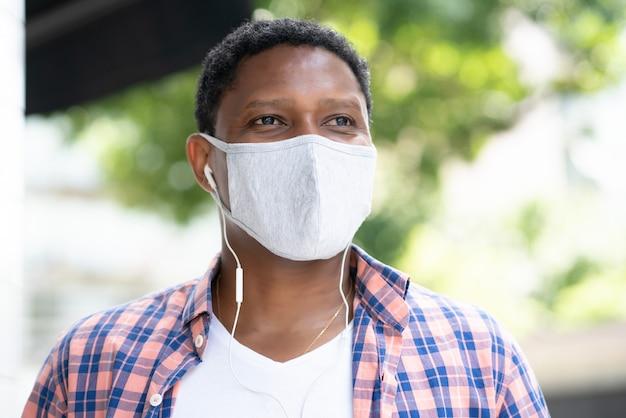 Afroamerikanermann, der eine gesichtsmaske trägt, während musik mit kopfhörern draußen auf der straße hört. neues normales lifestyle-konzept.