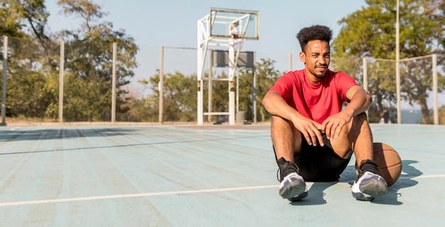 Afroamerikanermann, der eine pause nach einem basketballspiel hat