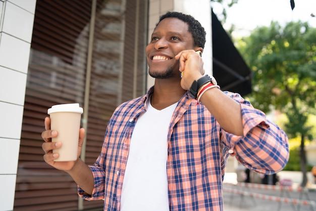 Afroamerikanermann, der eine tasse kaffee hält und am telefon spricht, während auf der straße geht