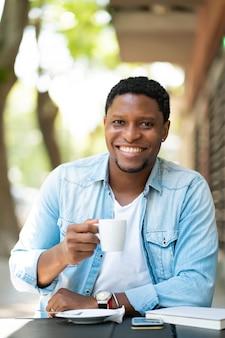 Afroamerikanermann, der einen kaffee genießt und trinkt, während er draußen im kaffeehaus sitzt