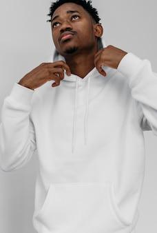 Afroamerikanermann, der einen weißen kapuzenpulli trägt