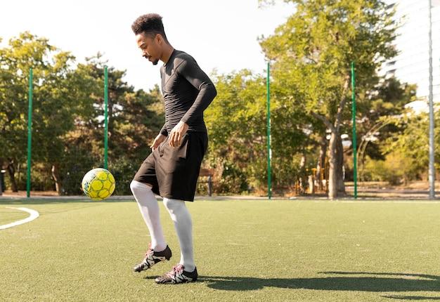 Afroamerikanermann, der fußball draußen spielt