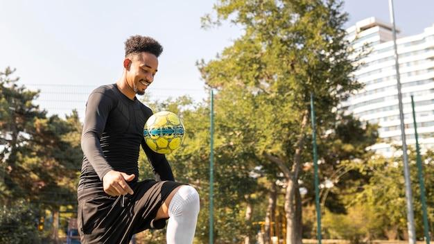 Afroamerikanermann, der fußball mit kopienraum spielt