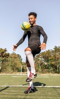 Afroamerikanermann, der fußball spielt