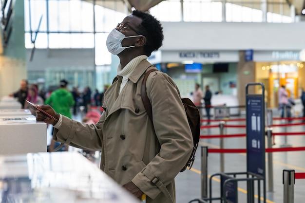 Afroamerikanermann, der gesichtsmaske im flughafen trägt