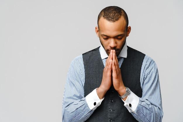 Afroamerikanermann, der hände im gebet hält und auf besseres hofft.