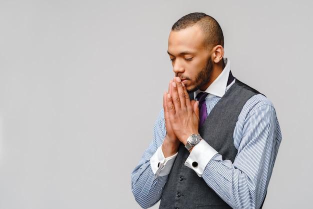 Afroamerikanermann, der hände im gebet hält und auf besseres hofft
